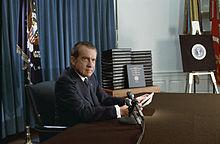 Nixon l'air grave est assis à son bureau devant une pile de classeurs.