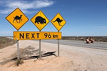 Warning signs stand out as the only feature alongside a road through a flat, treeless, landscape