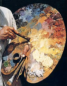 A man's finger sticks through a hole in a large wooden palette. One of his hands is dipping a brush into the paint and the other holds numerous brushes in reserve.