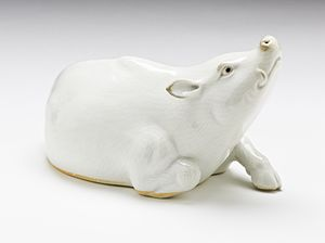 Okimono - Okimono of a reclining boar, Hirado Mikawachi porcelain with clear glaze, Edo period, 19th century
