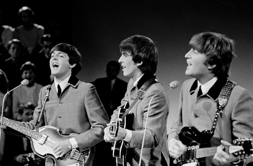 Paul McCartney, George Harrison, and John Lennon playing guitars and wearing matching grey suits