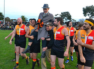 Australian rules football in popular culture - Singer-songwriter Paul Kelly, coach of the Espy Rockdogs, celebrates with his team after winning the Community Cup, an annual charity football match pitting musicians against radio personalities