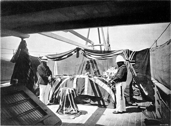 Black and white photograph of two men either side of a coffin draped in the Union Flag, surrounded by more flags, on board a ship.