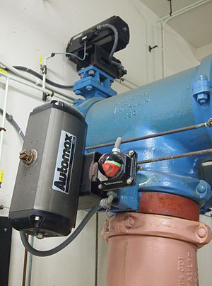 Solenoid valve - The solenoid valve (small black box at the top of the photo) with input air line (small green tube) used to actuate a larger rack and pinion actuator (gray box) which controls the water pipe valve.