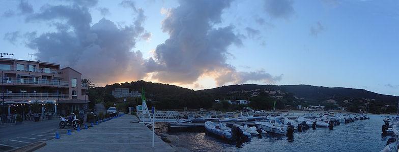 panorama montrant une petite marina avec des bateaux de petite taille et un hotel, en arriere plan des colines et des nuages éclairés par le soleil deja couché
