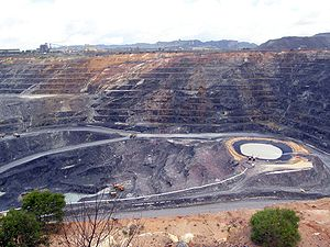 Uranium ore - Ranger 3 open pit, Northern Territory, Australia: Uranium mineralised Cahill Formation as visible in the pit is unconformably overlain by Kombolgie sandstone forming the mountains in the background