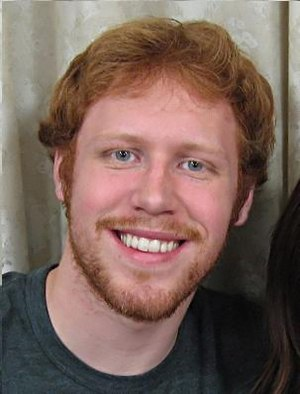A naturally red headed young man with a beard.