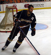Hockey player in black Anaheim ducks uniform. He skates near the goal with his stick on the ice.