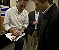Romney signs photos of himself for an audience member (5118372818).jpg