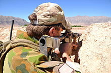 A man wearing a green camouflage uniform and a tan camouflage baseball cap looking through a rifle scope. He is resting his rifle on a dirt wall and steep mountains are visible in the background.