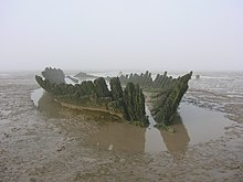 Wooden hulk of ship, surrounded by wet sand.