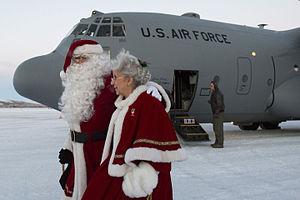 Operation Santa Claus - Santa and Mrs. Claus exit a C-130H Hercules aircraft at St. Mary's, Alaska, Dec. 5, 2015