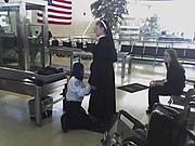 Passenger being screened by TSA employee in Detroit Metropolitan Wayne County Airport