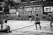 Several men playing a ball game; two of them jumping mid-air on either side of a net about eye-level high, appearing to be kicking the ball over the net; graffiti on a wall in the background