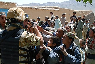 Generosity - Members of the Romanian Army sharing gifts with children in Afghanistan, 2009