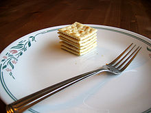 A plate, with a fork in the foreground and a stack of crackers in the background