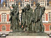 Six life-size bronze statues of men wearing robes and expressions of distress