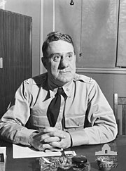 A man wearing a shirt and tie sits at a desk. On the desk are papers and a cigarette in an ash tray.
