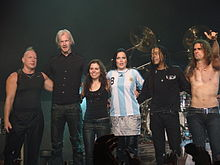Six band members, four male and two female, on stage at the end of a performance.
