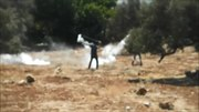 File:Tear gas grenades thrown back to soldiers using sling in Ni'lin.webm