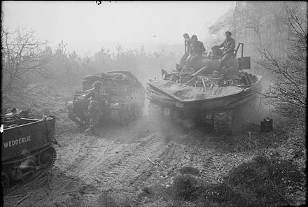 Sherman DD tank of the 44th Royal Tank Regiment, 4th Armoured Brigade, passing Universal Carriers of the 6th Battalion, King's Own Scottish Borderers east of the River Rhine, 25 March 1945. The British Army in North-west Europe 1944-45 BU2486.jpg