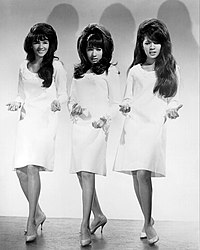 A black-and-white photograph of three women looking towards a camera. They all have large black hair and all wear short white dresses and heels.