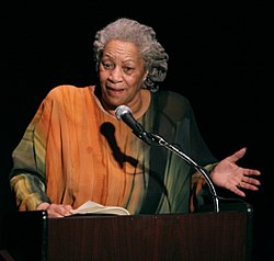 Photograph of Toni Morrison, showing her in an orange and green dress with her gray hair pulled back. She is speaking at a podium and gesturing.
