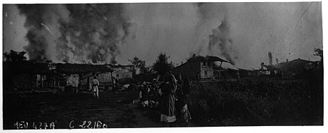 Burning buildings, with residents watching