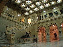 Marble lobby with statues, columns and a flight of steps