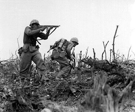 U.S. Marine Sgt. John Wisbur Bartlett Sr. fires on a Japanese position using an M1 Thompson submachine gun during an advance on Okinawa in 1945. USMC Okinawa Thompson.JPEG