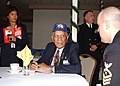 US Navy 030207-N-8894M-007 1st Lt. William B. Ellis, a Tuskegee Airmen in World War II assigned to the Fighting 99th, 332nd Fighter Wing, signs an autograph.jpg