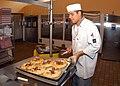 US Navy 040831-N-2976H-002 Culinary Specialist Seaman Apprentice Jorge Garcia prepares to slice freshly baked pizzas.jpg