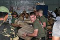 US Navy 050104-M-9792P-027 U.S. Marines work with Indonesian Military personnel and International Aid workers to sort and distribute humanitarian relief supplies stored in a warehouse at Palonia Air Field in Medan, Indonesia.jpg