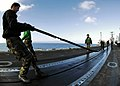 US Navy 051104-N-4166B-015 An airman assigned to the Air Department aboard the Nimitz-class aircraft carrier USS Abraham Lincoln (CVN 72), stretches a steam-powered catapult slot seal as they seal-off the catapult from debris a.jpg