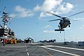 US Navy 061023-N-6106R-135 An MH-60S Seahawk sets munitions on the flight deck aboard USS Kitty Hawk during a vertical replenishment with Military Sealift Command ammunition ship USNS Flint (T-AE 32).jpg