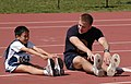 US Navy 070422-N-5215E-002 Midshipman 3rd Class Nicholas Lowe shows Julian Than how to stretch before running in the Special Olympics at the Naval Academy.jpg