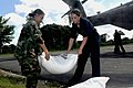 US Navy 080912-N-5642P-101 Hospital Corpsman 3rd Class Reyln Pandophino and Seaman Courtney Cresta, both assigned to the amphibious assault ship USS Kearsarge (LHD 3), help unload rice bags from a CH-53 Super Stallion.jpg