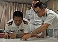 US Navy 100608-N-2218S-002 Lt. j.g. Jason DeJesus, navigator of the guided-missile destroyer USS Mustin (DDG 89), reviews navigation charts with Cmdr. Masahiro Takao and Lt. Kosuke Okazaki.jpg