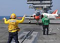 US Navy 100613-N-3885H-158 A Sailor directs a T-45A Goshawk as it prepares for launch from USS George H.W. Bush (CVN 77).jpg