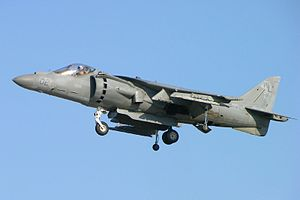 Port view of grey jet aircraft hovering with landing gear extended. The two engine exhaust nozzles on each side and directed down.