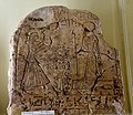 Upper part of a stela showing a standing man adoring Ra-Horakhty who holds a was-sceptre. 19th Dynasty. From Egypt. The Petrie Museum of Egyptian Archaeology, London.jpg