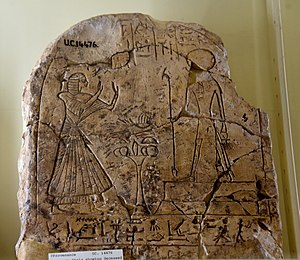 Was-sceptre - Upper part of a stela showing a standing man adoring Ra-Horakhty who holds a was-sceptre. 19th Dynasty. From Egypt. The Petrie Museum of Egyptian Archaeology, London