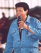 A color photograph of Chubby Checker standing with a microphone