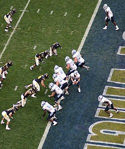 Several American football players in white and navy uniforms in action at the end zone area of the field.