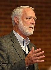 En vithårig och vitskäggig man som gester med sin högra hand medan han talar