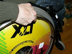 A close-up of a rear wheel of a wheelchair.