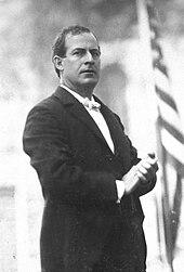 Tre fjerdedeler stående portrett av Bryan i mørk dress og hvitt slips, med hendene sammenklappet foran seg, og med et seriøst og kommanderende uttrykk