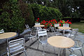 'Hortorum' pelargonium with cafe tables and chairs Gibberd Garden Essex England 01.JPG