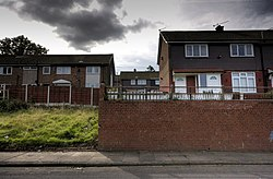 A roadside view of several 20th-century British houses. The houses are set high above the roadside. A grass slope is visible to the lower left of the image, and a tall brick wall to the lower right. A gap in the centre of the image indicates the absence of a single house