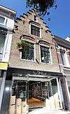 foto van Huis met gecementeerde trapgevel. De treden afgedekt met natuurstenen platen. Cijferankers (163). Moderne pui